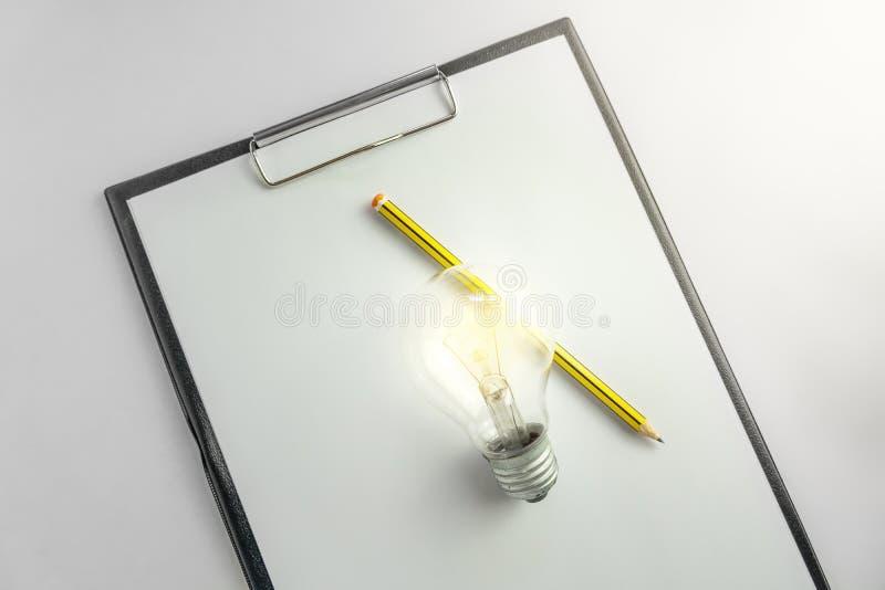 Carta in bianco con una lampadina e concetto aspettante di idea della matita con luce fotografia stock
