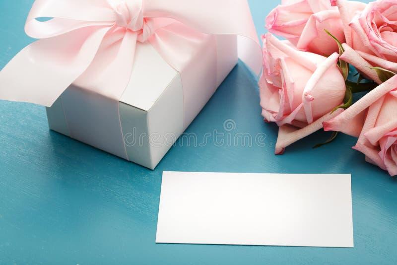 Carta in bianco del messaggio con il contenitore e le rose di regalo immagini stock