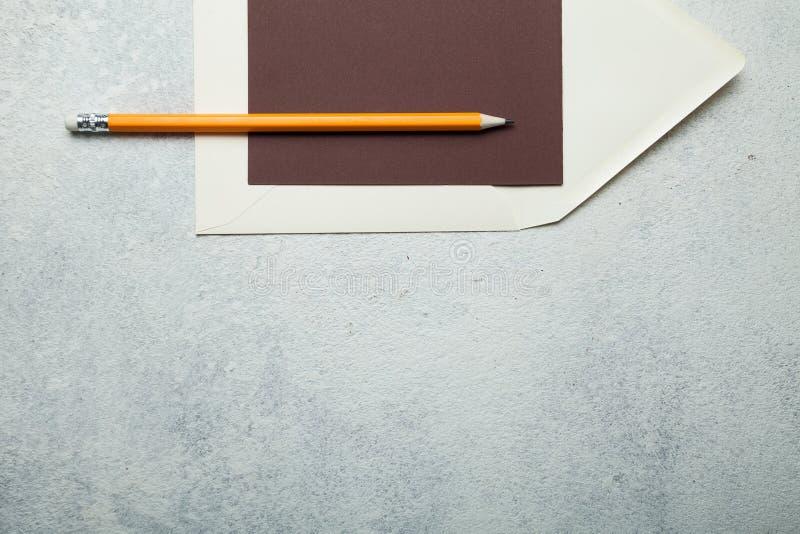 Carta in bianco per marrone del testo, busta beige e matita ha contro fondo bianco fotografia stock libera da diritti