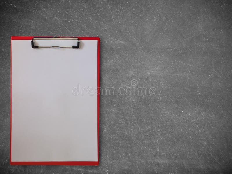 Carta in bianco sulla lavagna per appunti, su una lavagna fotografia stock libera da diritti