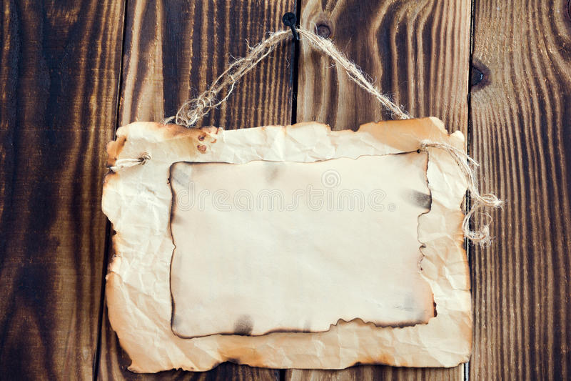 Carta bruciacchiata d'attaccatura su un fondo di legno immagine stock
