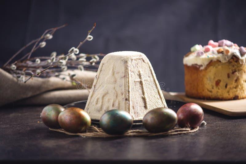 Carta con i dessert tradizionali e le uova variopinte nello stile rustico su un fondo scuro Pasqua felice immagine stock libera da diritti