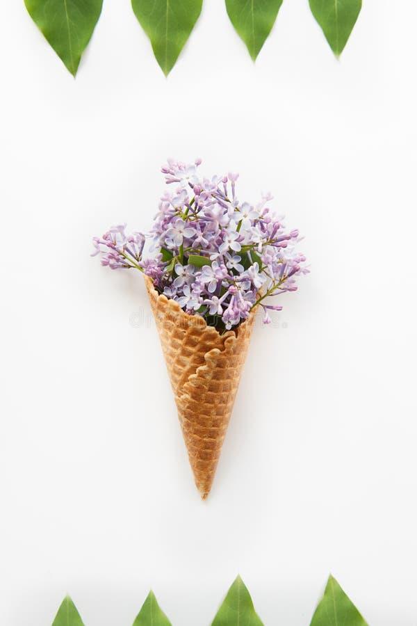 Carta con la fine sul mazzo dei fiori lilla porpora nel cono della cialda e nel telaio dei raws delle foglie verdi sui precedenti fotografie stock