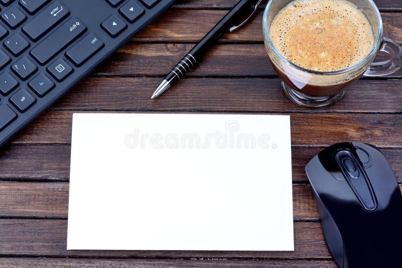 Carta con la tazza e la tastiera di caffè su fondo di legno fotografia stock