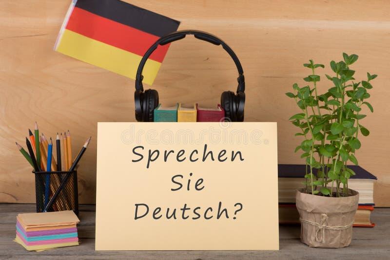 carta con testo & x22; sprechen il sie deutsch? & x22; , bandiera della Germania, libri, cuffie, matite fotografia stock