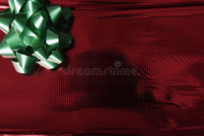 Carta da imballaggio rossa lucida con l'arco verde immagini stock libere da diritti