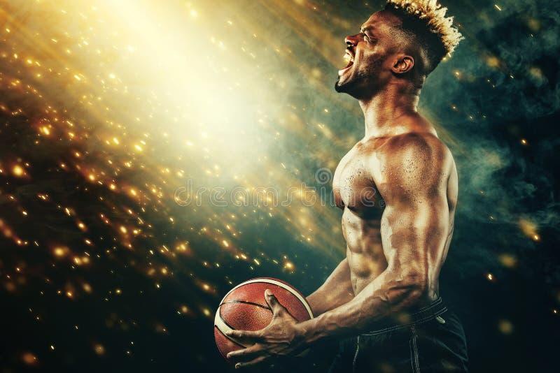 Carta da parati di pallacanestro Ritratto dello sportivo afroamericano, giocatore di pallacanestro con una palla sopra fondo nero fotografie stock