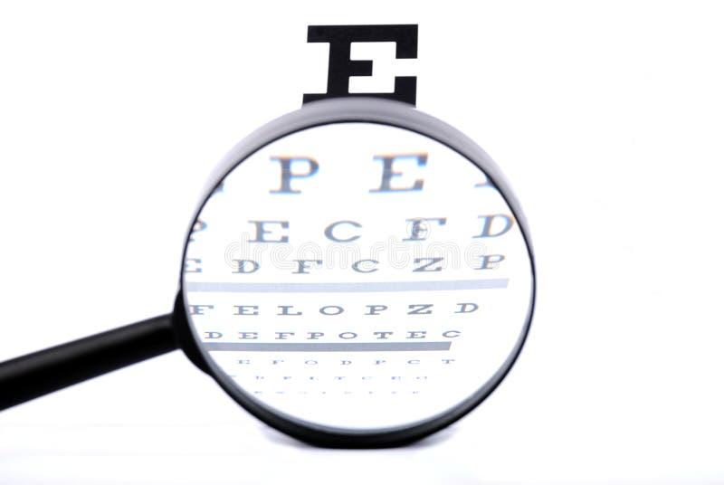 Carta de olho através de um magnifier imagem de stock