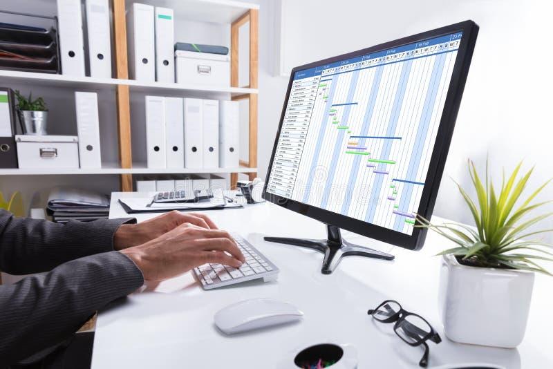 Carta de Working On Gantt do empresário usando o computador imagens de stock royalty free