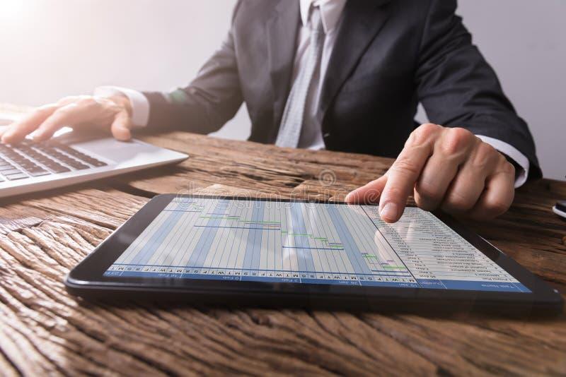 Carta de Working With Gantt do homem de negócios na tabuleta de Digitas fotos de stock royalty free