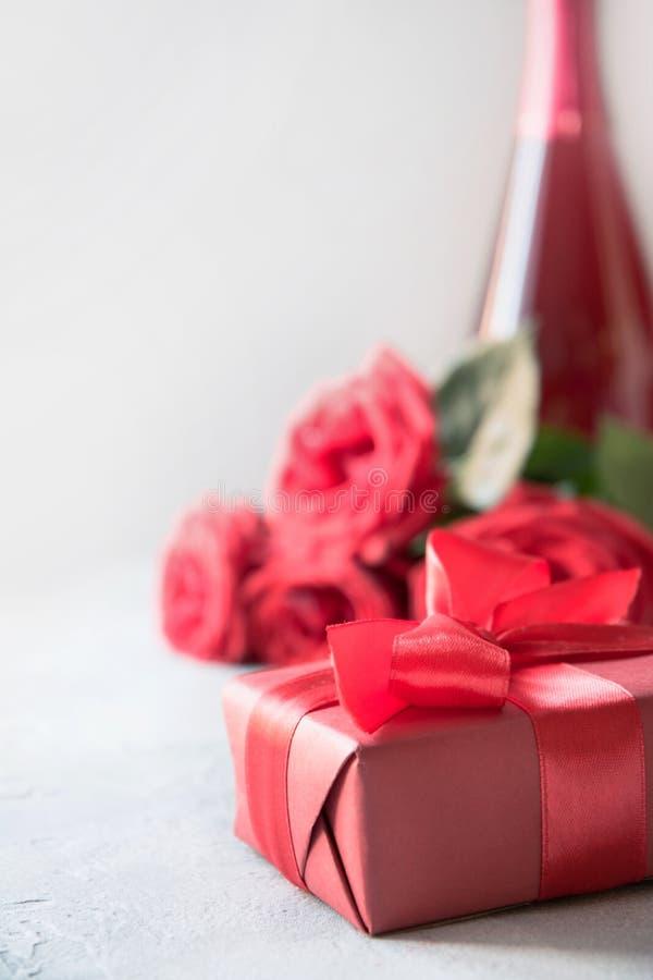Carta dei biglietti di S. Valentino con il contenitore di regalo rosso, rose, bottiglia del champagne su bianco Spazio per testo immagine stock libera da diritti