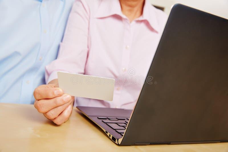 Carta del cliente della tenuta della mano mentre comperando online immagini stock