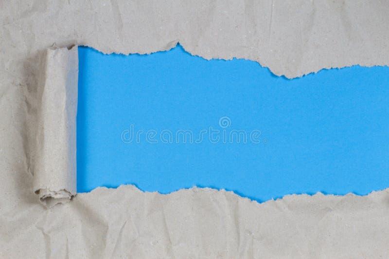 Carta del pacchetto di Brown lacerata rivelare fondo blu con lo spazio della copia immagini stock