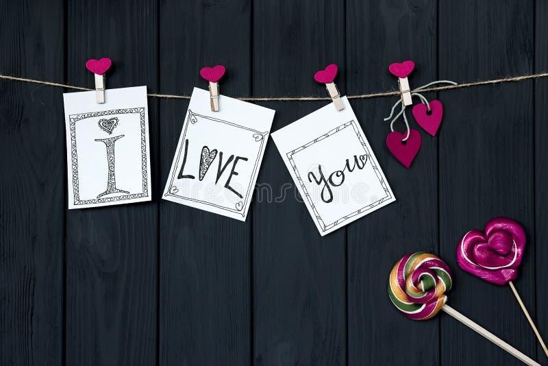 Carta del ` s del biglietto di S. Valentino con un cavo del ` del ` del messaggio ti amo ed i perni rosa con i cuori del caramell immagini stock