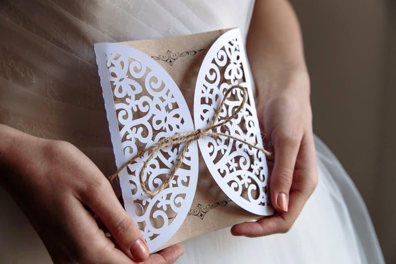 Carta dell'invito di nozze in mani immagini stock