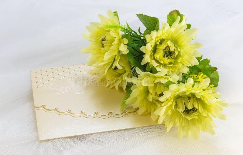 Carta dell'invito e un mazzo dei fiori artificiali su tul bianco immagini stock libere da diritti