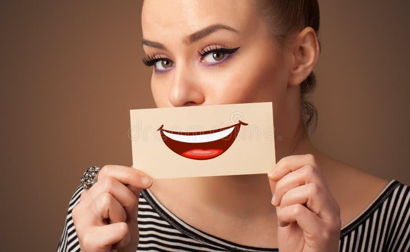 Carta della tenuta della persona davanti alla sua bocca immagini stock