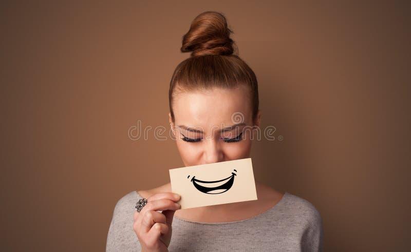 Carta della tenuta della persona davanti alla sua bocca fotografia stock