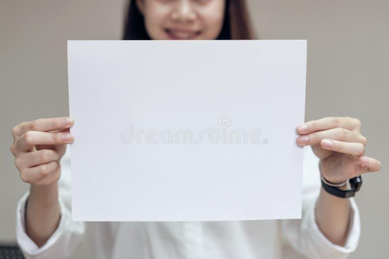 Carta di bianco dello spazio in bianco della tenuta della donna di affari per l'insegna del testo immagini stock libere da diritti