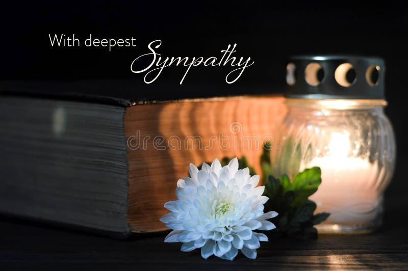 Carta di compassione con il fiore, la candela ed il libro commemorativi fotografia stock libera da diritti