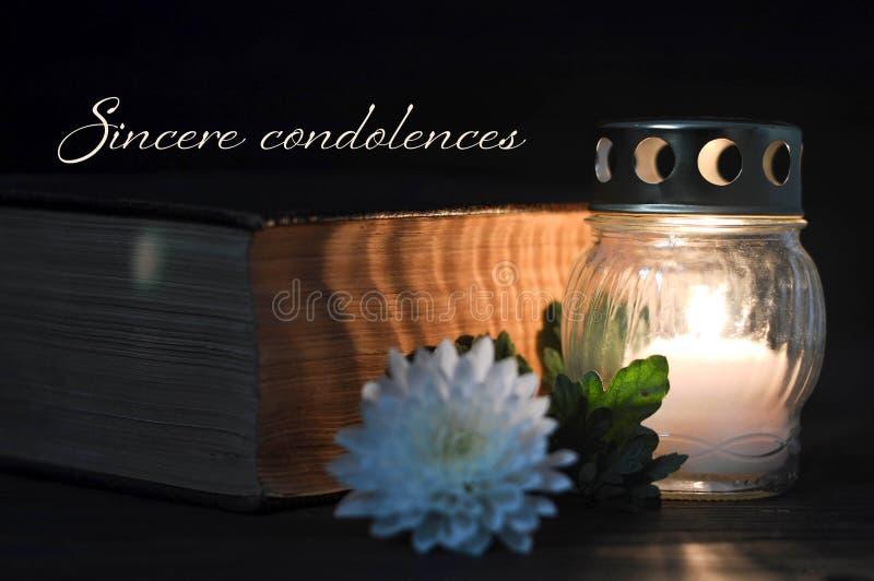 Carta di condoglianza con la candela commemorativa, il fiore bianco ed il libro Condoglianze sincere immagini stock