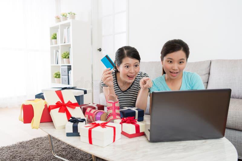Carta di credito allegra della tenuta della donna che indica computer portatile fotografia stock