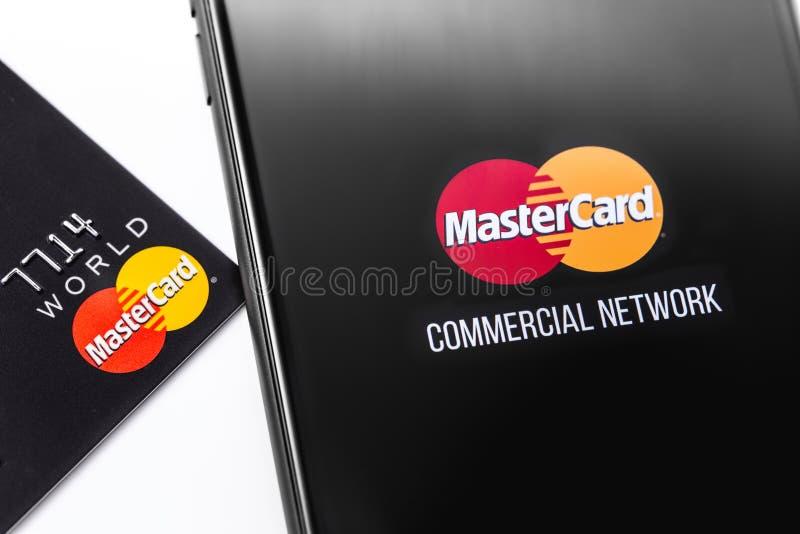 Carta di credito del primo piano e smartphone con il logo di Mastercard sullo schermo fotografie stock libere da diritti