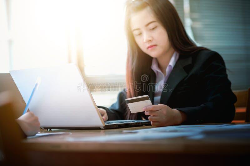 Carta di credito della tenuta della donna di affari e computer portatile usando Su fotografia stock