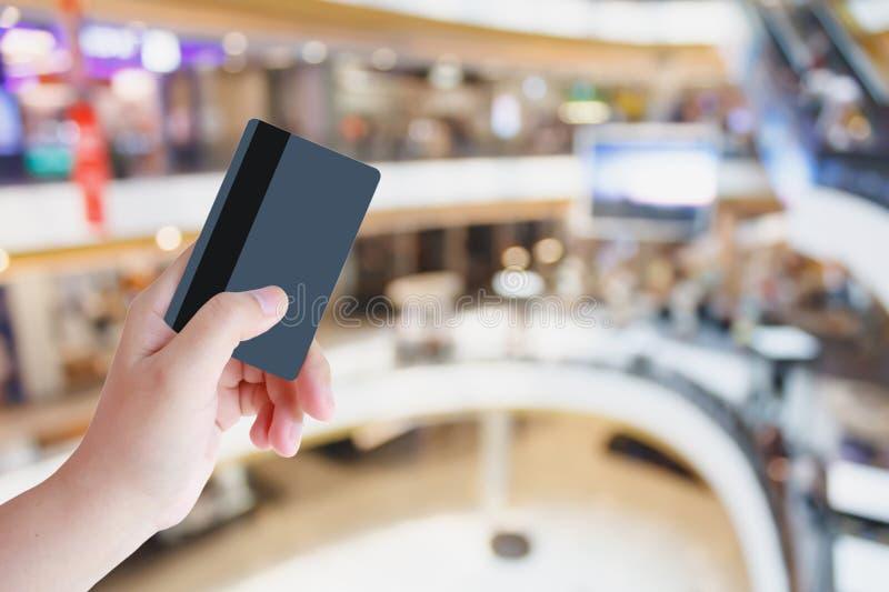 Carta di credito della tenuta della mano con il centro commerciale immagine stock