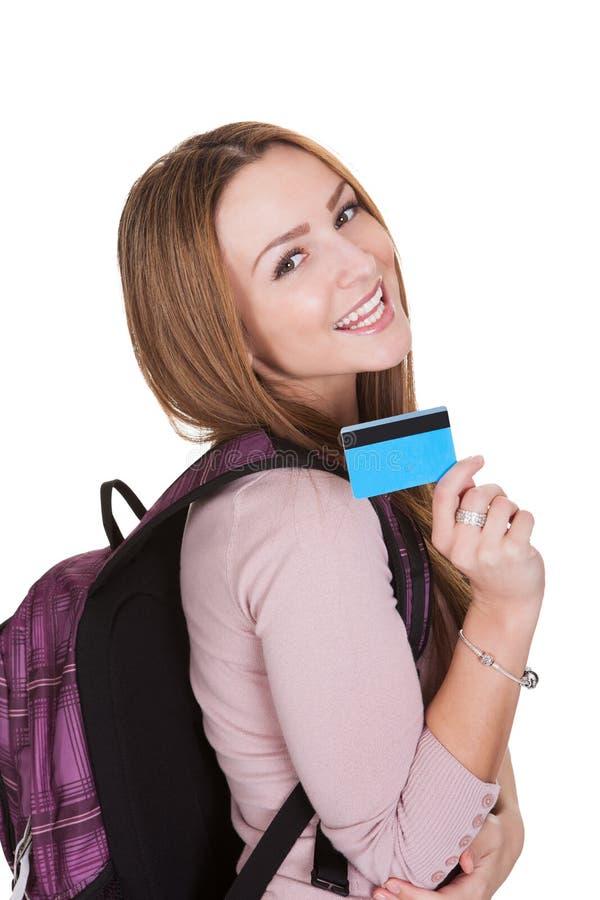 Carta di credito della tenuta della studentessa sopra fondo bianco fotografia stock