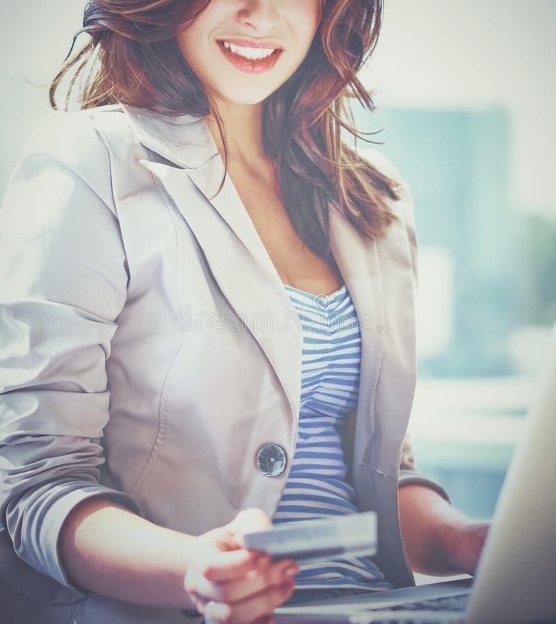 Carta di credito della tenuta della donna sul computer portatile per acquisto online immagine stock