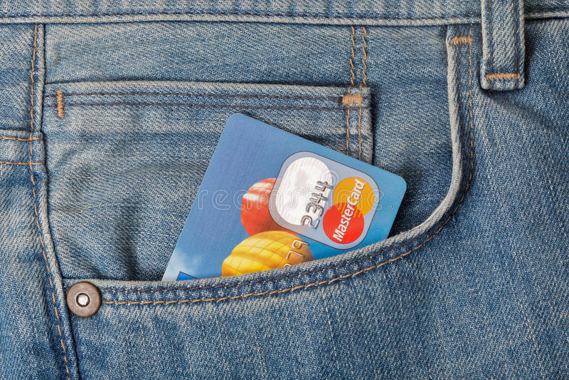 Carta di credito di Mastercard in tasca del primo piano delle blue jeans immagini stock