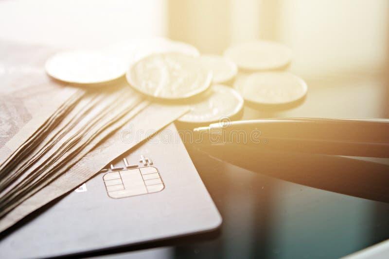 Carta di credito, soldi, monete e penna sulla tavola della scrivania fotografie stock libere da diritti