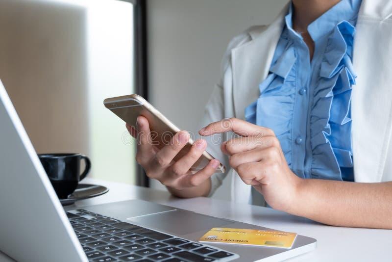 Carta di credito di uso della donna per acquisto online sul suoi computer portatile e telefono fotografia stock libera da diritti