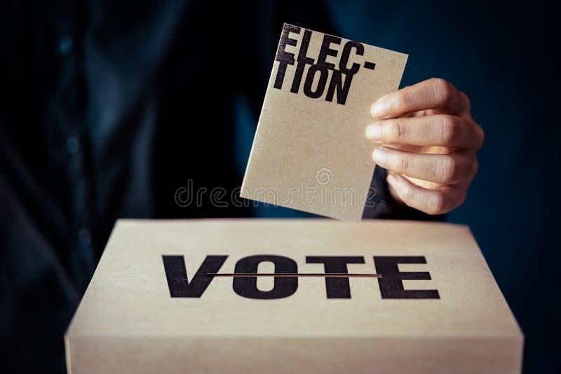 Carta di elezione della tenuta della mano e scatola di voto, concetto di democrazia immagini stock
