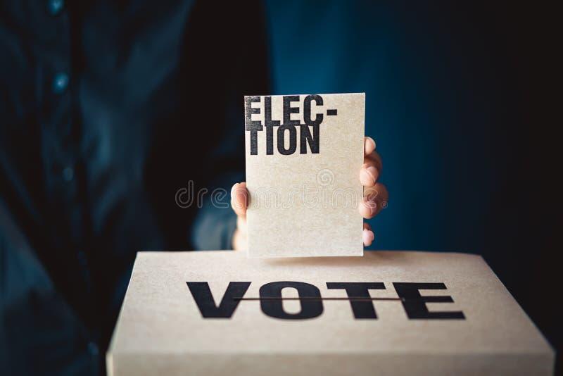 Carta di elezione della tenuta della mano e scatola di voto, concetto di democrazia fotografia stock libera da diritti