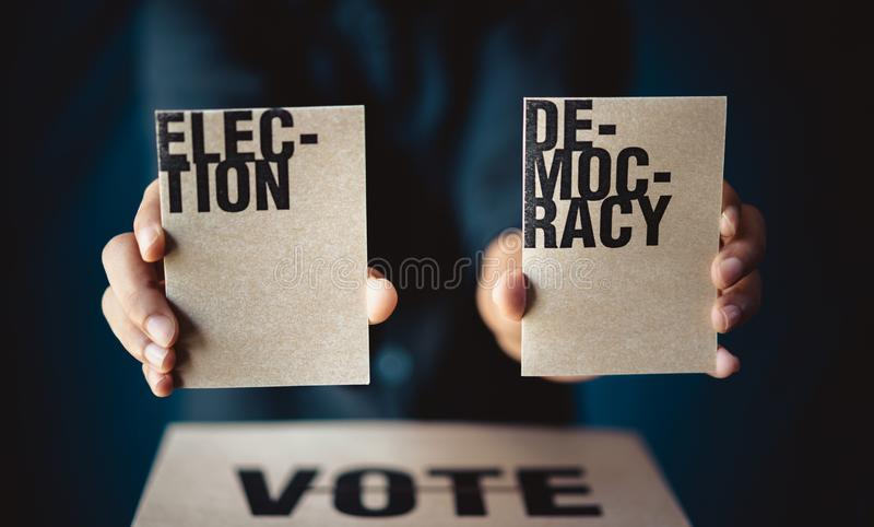 Carta di elezione della tenuta della mano e scatola di voto, concetto di democrazia immagine stock libera da diritti