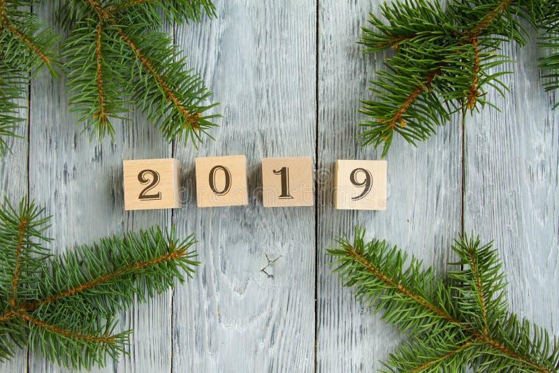 Carta di festa del ` s del nuovo anno i cubi di legno con le figure dell'anno su un fondo di legno grigio, accanto ad abete si ra fotografia stock libera da diritti
