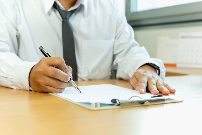 Carta di firma del contratto dell'uomo d'affari con la penna in scrivania immagine stock libera da diritti