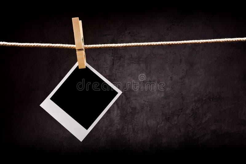 Carta di fotografia con la struttura istantanea della foto allegata alla corda con fotografie stock