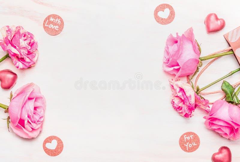 Carta di giorno di biglietti di S. Valentino con le rose, il cioccolato ed il messaggio di amore su fondo di legno bianco, vista  immagine stock