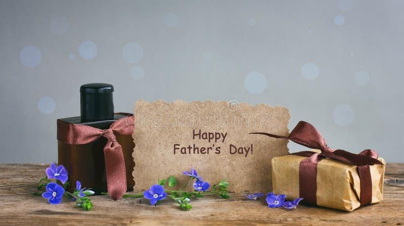 Carta di giorno di padri, contenitore di regalo con il nastro marrone, bottiglia di profumo, PA immagini stock libere da diritti