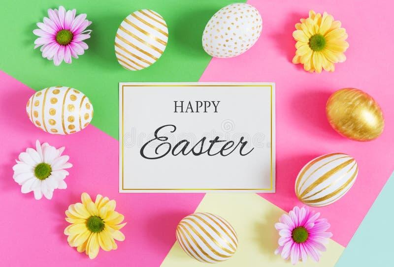 Carta di regalo con le uova di Pasqua variopinte e i camomiles fotografia stock