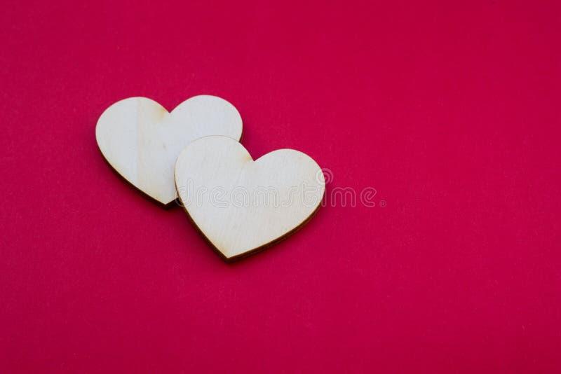 Carta di San Valentino con un simbolo di legno di due cuori su surfac rosso fotografia stock libera da diritti