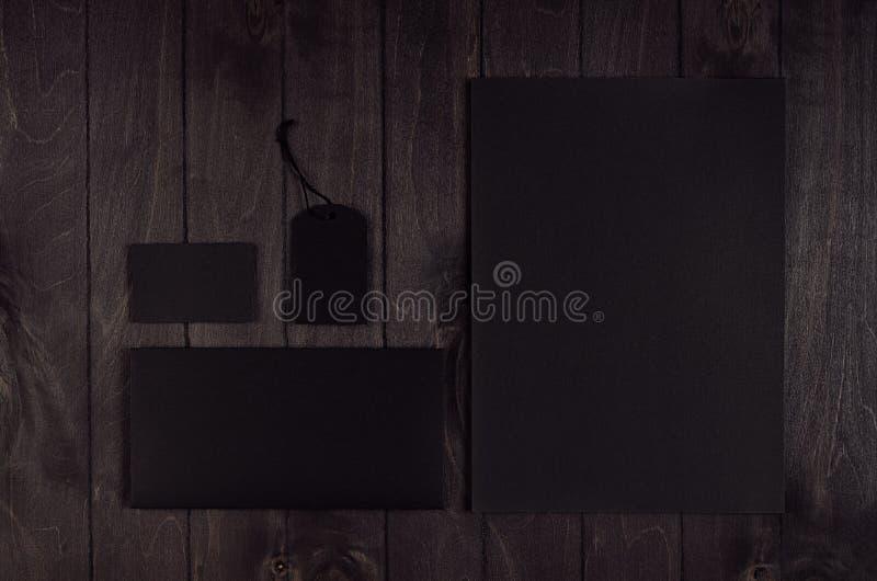 Carta intestata nera in bianco, etichetta, busta, biglietto da visita sul bordo di legno scuro fotografia stock libera da diritti