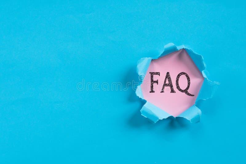 Carta lacerata blu che rivela carta rosa con la parola del FAQ fotografia stock
