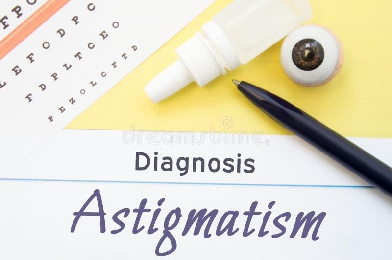 A carta para testar a acuidade visual, as gotas de olho e o modelo anatômico do olho encontra-se ao lado do astigmatismo do diagn foto de stock