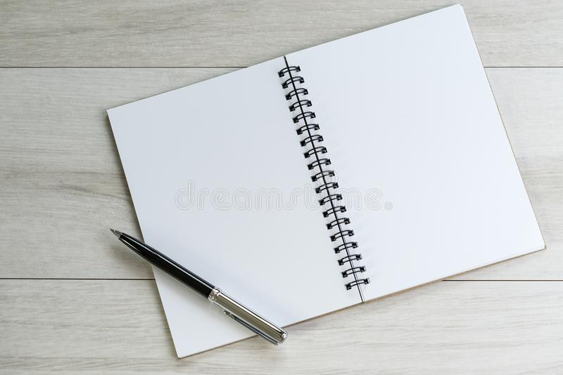 Carta per appunti e penna in bianco bianche d'apertura a sinistra con su luce fotografia stock libera da diritti