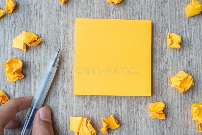 Carta per appunti gialla vuota con la penna di tenuta dell'uomo d'affari e carta sbriciolata sul fondo di legno della tavola Spaz immagini stock