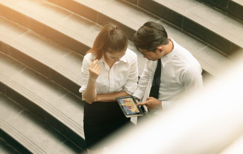 Carta punteaguda del hombre de negocios en la pantalla de la tableta y el togethe del análisis fotografía de archivo libre de regalías
